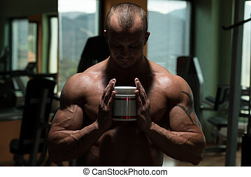 Bodybuilder Posing With Supplements For Copy Space -...