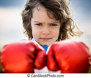 Kid wearing red boxing gloves. Girl power and feminism...