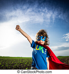 Superhero kid against dramatic blue sky background