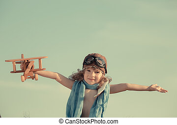 Happy kid playing with toy airplane against summer sky...