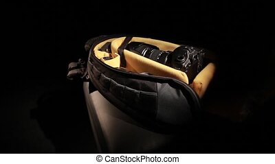 Camera bag - a camera is reached from a bag on a dark...