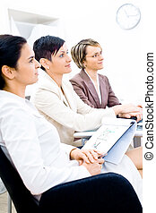 Business Training - Three businesswoman attending on...