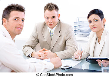 Businessteam of three working together, sitting around a...
