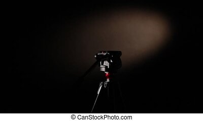 Camera and tripod - setting of camera on a tripod on a dark...