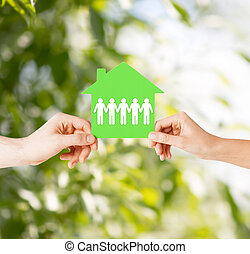 man and woman hands with paper house - real estate and...