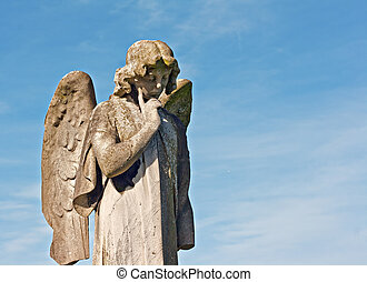 Winged angel statue in graveyard