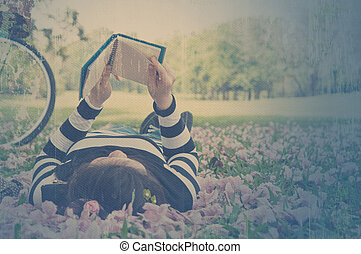 Asian woman reading booklet on the grass Vintage style