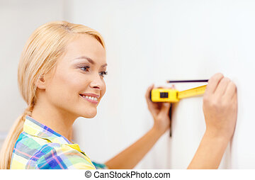 smiling woman measuring wall - repair, building and home...