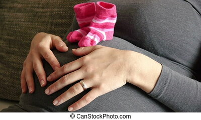 Pregnant woman with baby socks touching belly on sofa