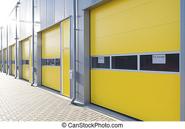 commercial warehouse with yellow roller doors with a for...