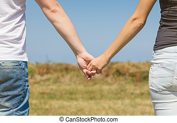 Close up of love couple holding hands outdoors - Back view...