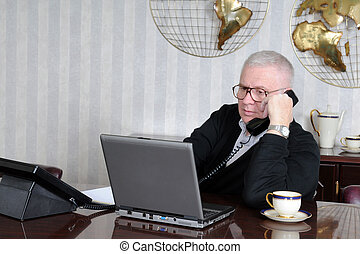 Senior Businessman at Work - A senior businessman talking on...