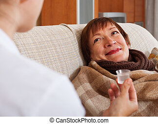 nurse caring for sick mature woman at home