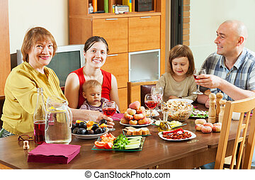multigeneration family together over celebratory table -...