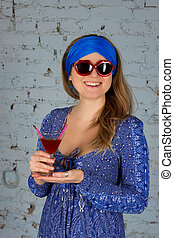 woman drinking a cocktail - woman with sunglasses drinking a...