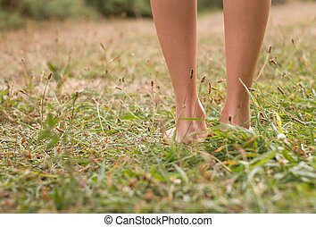Young female legs walking on the grass