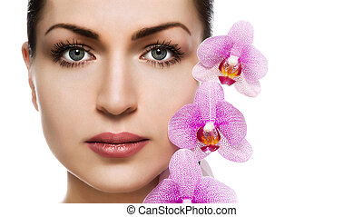 Portrait of a beautiful girl with perfect skin and orchid