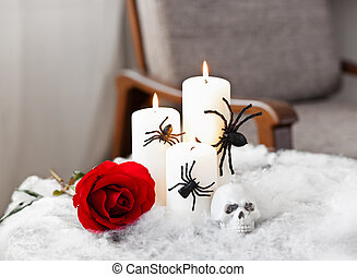 Grey upholstered chair in Halloween setting with candles