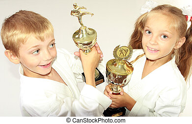 Girl and boy in a kimono with a championship winning in the...