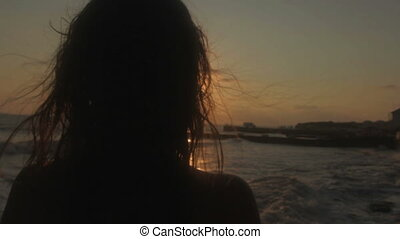 Silhouette of young woman in sunset