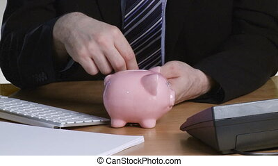 Businessman putting money in his piggy bank - Businessman...