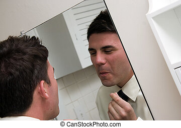 Checking Himself in the Mirror - A young main in a shirt and...
