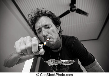 smoker - Young man lighting up a cigarette in hotel room
