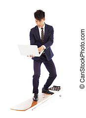 businessman using a laptop on a  surfboard