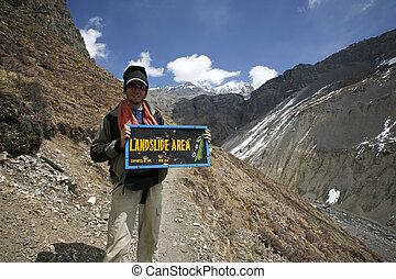 landslide - man holding a landslide warning sign, annapurna,...