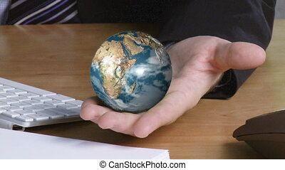 Hand holding a globe - Globe rotating in a businessperson...