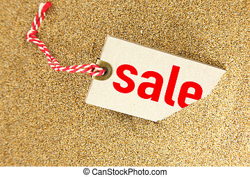 Big sale tag on sand closeup