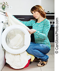 Unhappy woman doing laundry with washing machine at home...