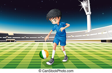 A boy at the field using the ball with the flag of Ireland