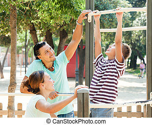 Family of three training on chin-up bar bar - Family of...