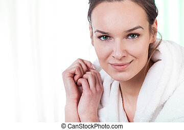 Woman wearing bathrobe - Woman smiling at camera at home...