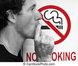 stop smoking - man smoking a no-smoking sign