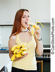 long-haired girl eating banana at home kitchen