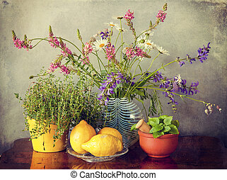 wild flowers in vase, herbs and lemon fruits - Garden herbs,...