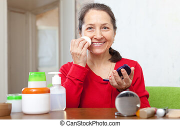 mature woman in dress puts facepowder on face - Happy mature...