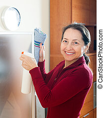 Smiling mature woman cleaning glass with rag and cleanser