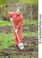 Mature woman working with shovel in orchard