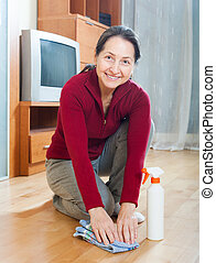 Smiling mature woman rubing floor with furniture polish at...