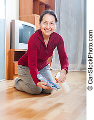mature housewife polishing parquet floor with furniture...