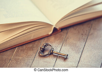 Retro key and opened book on wooden table