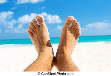 tropical paradise - picture of male legs over tropical beach...