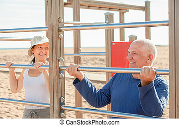 senior man and mature woman training with pull-up bar -...