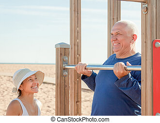Mature couple together training on pull-up bar in summer