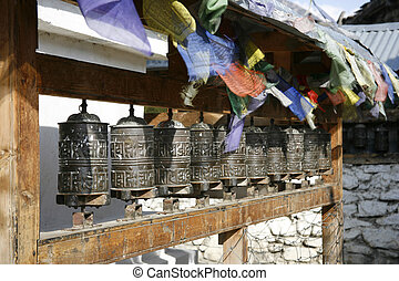 wheels - praying wheels and flags in manang, annapurna,...