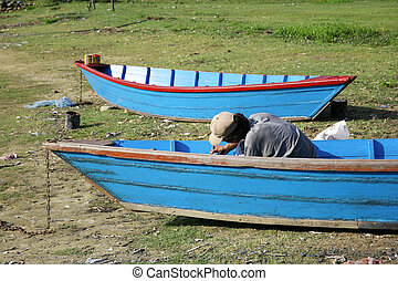 man painting his blue boat, pokhara, nepal