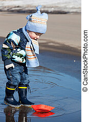 Little boy plays with paper ships in a spring puddle